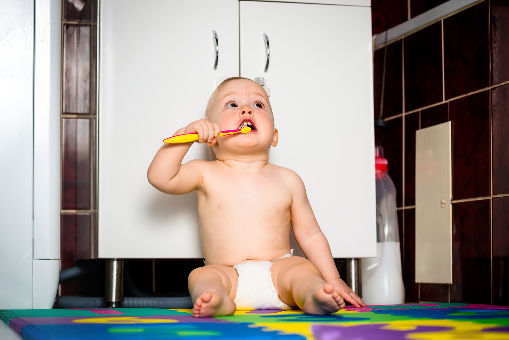 Baby cleaning teeth in bathroom