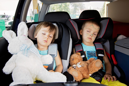 Two boys in car seats, travelling, sleeping in the car with teddy bears