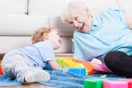 Grandmother cheerfully playing with her grandson indoors
