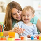 child boy and woman painting in daycare or nursery or playschool