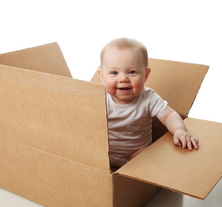 Portrait of a cute baby sitting in a brown cardboard box